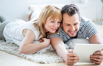 Young couple on bed using tablet device together